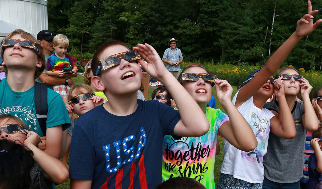 Kids watching an eclipse through paper safety glasses